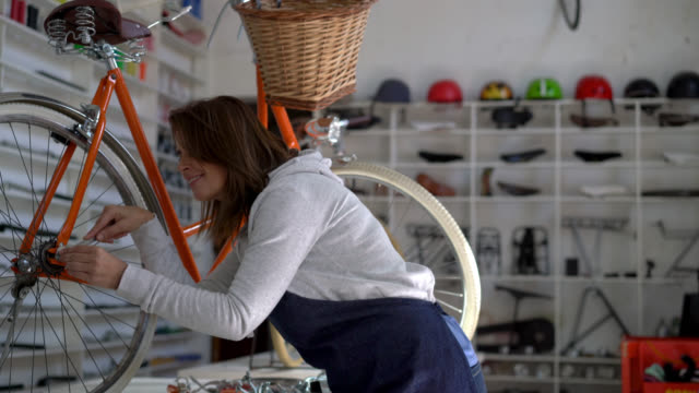 woman at a bicycle repair shop putting a vintage bike together using a tool and a screw - aggiustare video stock e b–roll