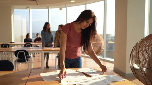 コワーキングオフィスの女性が笑顔で書類を手配 - casual clothing点の映像素材/bロール