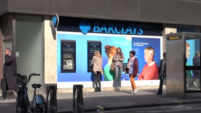 woman at atm outside barclays bank branch in baker street central london - メリルボーン点の映像素材/bロール