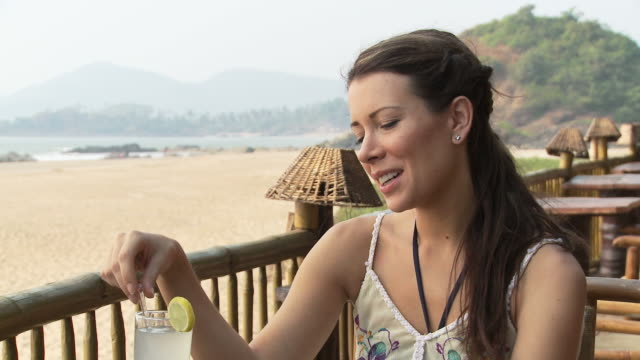 Woman at beach bar, talking to someone who is off camera