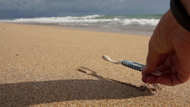 vídeos de stock e filmes b-roll de woman at beach removing plastic pollution toothbrush environmental cleanup - escova de dentes