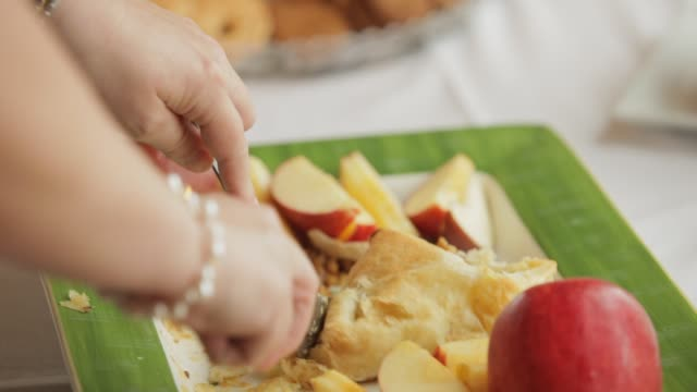woman at buffet table slicing into pastry at a baby shower party - baby shower video stock e b–roll