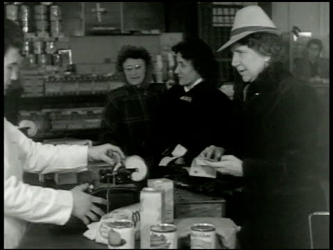 woman at check out counter in small shop going through ration points book cu tearing numbers of book two women standing bg wwii rationing - food stamps stock videos & royalty-free footage