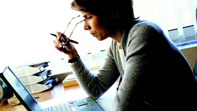 overexposed woman at desk takes off glasses + looks at laptop, puts glasses back, types + writes - overexposed video stock e b–roll