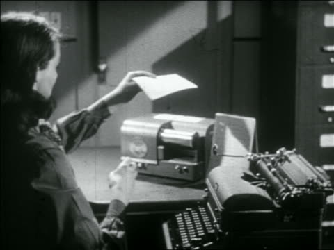 vidéos et rushes de b/w 1956 woman at desk taking sheet of paper from typewriter + inserting it in early fax machine - 1956