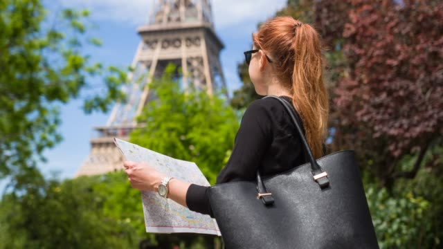 Woman at garden of Champ de Mars in Paris, looking at Eiffel Tower