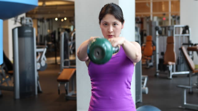 vidéos et rushes de woman at gym, performing resistance exercises with weights. - une seule femme d'âge moyen