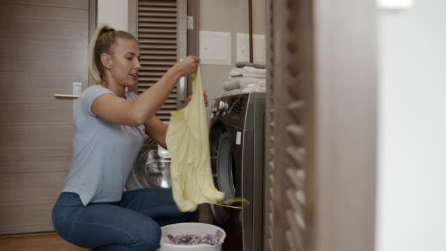 frau zu hause tun die wäsche und legen die kleidung in der waschmaschine - wäsche stock-videos und b-roll-filmmaterial
