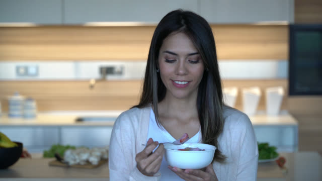 woman at home enjoying a bowl of strawberries and yogurt while looking at camera smiling - yoghurt stock videos & royalty-free footage