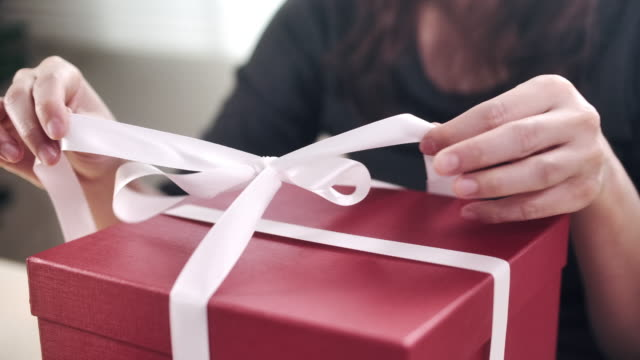 woman at home opens a gift bag that has arrived. the package can be a gift or an order arrived thanks to online shopping. concept of: shopping, love, gift, anniversary. - unwrapping stock videos & royalty-free footage