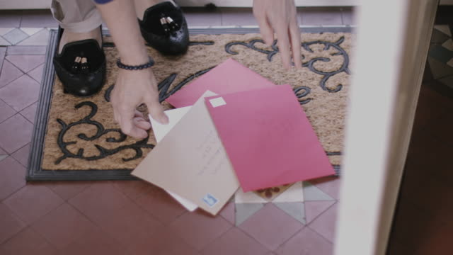 Woman at home picking up letters on doormat