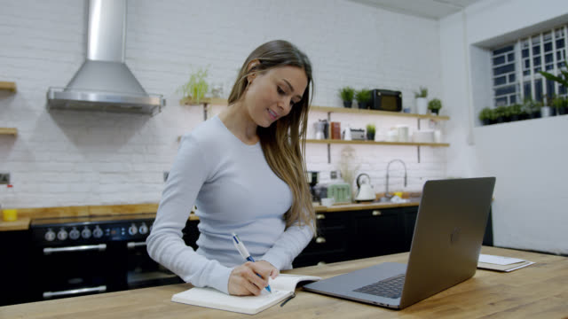 woman at home taking notes on her agenda while looking at laptop screen - report stock videos & royalty-free footage