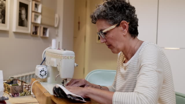 woman at home using a sewing machine. - pollution mask stock videos & royalty-free footage