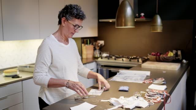 diyマスクのための仕分け布を使用して自宅で女性。 - パタンナー点の映像素材/bロール