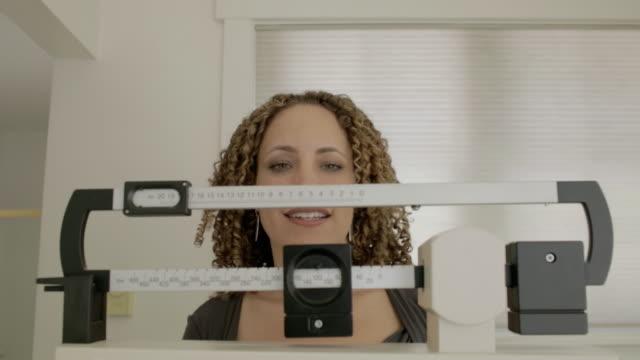 vídeos de stock e filmes b-roll de woman at home - balança instrumento de pesagem