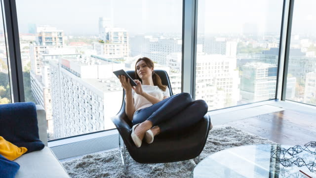 ms woman at home with digital tablet in penthouse apartment - zurücklehnen stock-videos und b-roll-filmmaterial