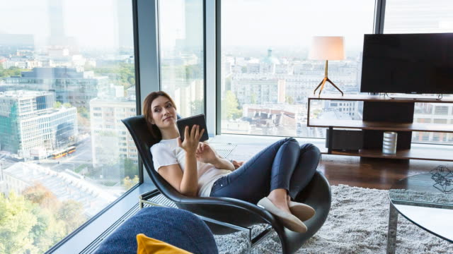 ms pan woman at home with digital tablet in penthouse apartment - wohnung stock-videos und b-roll-filmmaterial