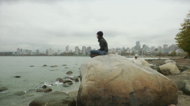 ws woman at kitsilano beach sitting on boulder, skyline in background / vancouver, british columbia, canada - boulder rock bildbanksvideor och videomaterial från bakom kulisserna