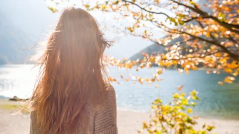 stockvideo's en b-roll-footage met vrouw op lakeside in de herfst op zoek in de verte - autumn