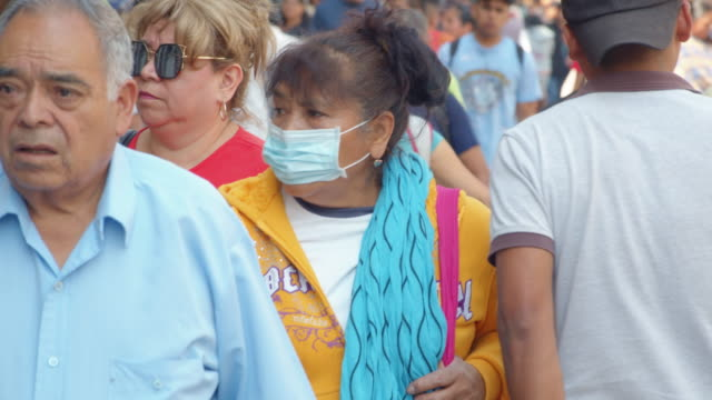 vidéos et rushes de woman at mexico city wearing mask during coronavirus crisis. people walking in crowded walkway. slow motion - latino américain