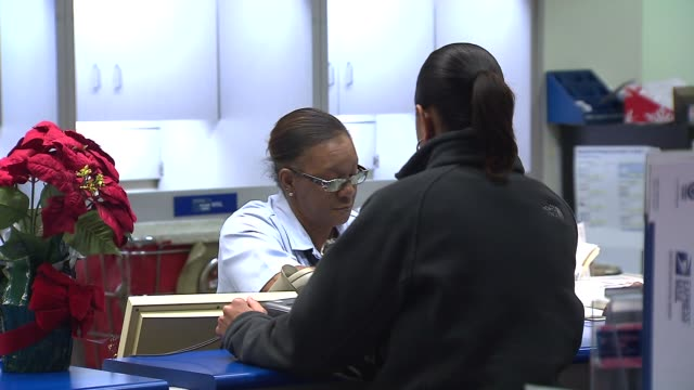 woman at post office counter on december 09, 2013 in chicago, illinois - post office stock videos & royalty-free footage