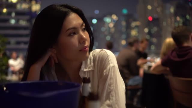 Woman at restaurant table in Dubai, trucking shot