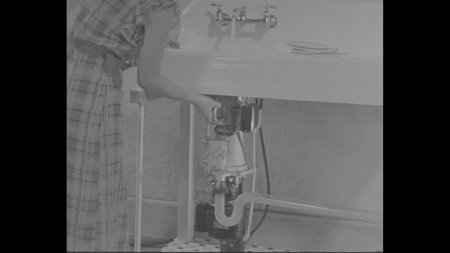 woman at sink demonstrates a new way to get rid of food garbage, the general electric garbage disposal, with hand turning crank on disposal below... - ジェネラルエレクトリック点の映像素材/bロール