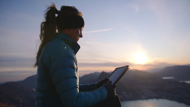 woman at sunset in winter jacket uses digital tablet on top of mountain - warm clothing stock videos & royalty-free footage