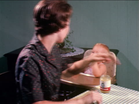 1960 woman at table feeding baby girl in high chair from jar of baby food / industrial - 1960 stock videos & royalty-free footage