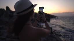 Woman at the beach photographing the sunset