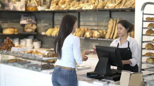 Vrouw aan de kassa van het betalen van een bakkerij