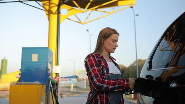 woman at the gas station - fare il pieno di benzina video stock e b–roll