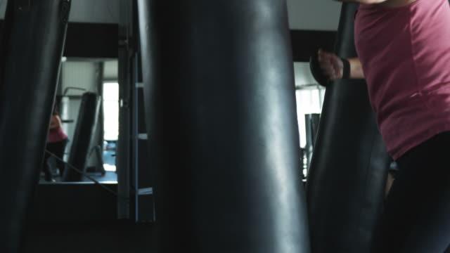 vídeos de stock, filmes e b-roll de woman at the gym punching a heavy bag - posição de combate