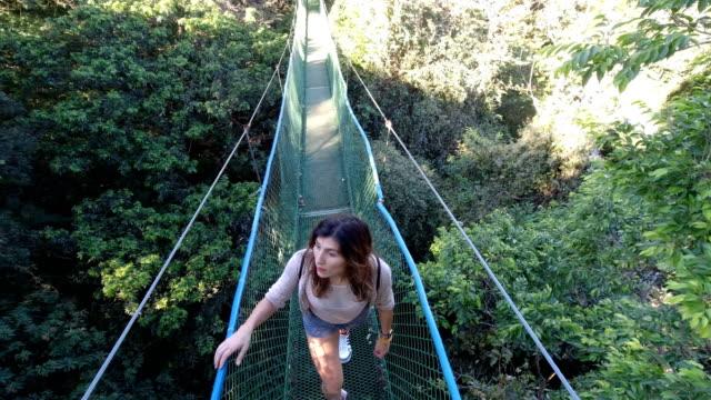 vídeos y material grabado en eventos de stock de mujer en los puentes colgantes en la selva tropical - puente colgante