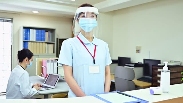 病院の受付で顔の盾を身に着けている女性 - nurse点の映像素材/bロール
