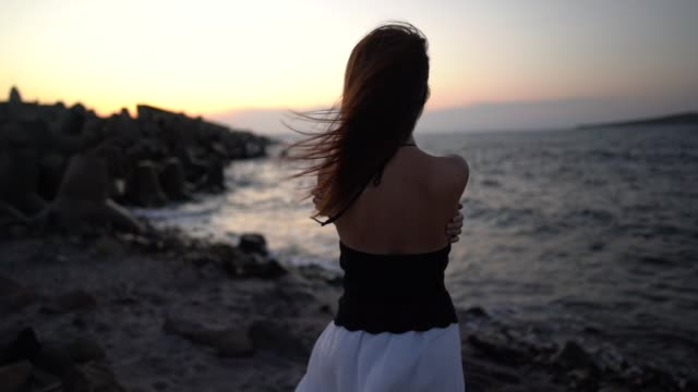 woman at the seashore staring the sunset - windswept stock videos & royalty-free footage