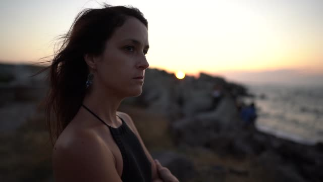 stockvideo's en b-roll-footage met vrouw bij de kust die de zonsondergang staart - staring