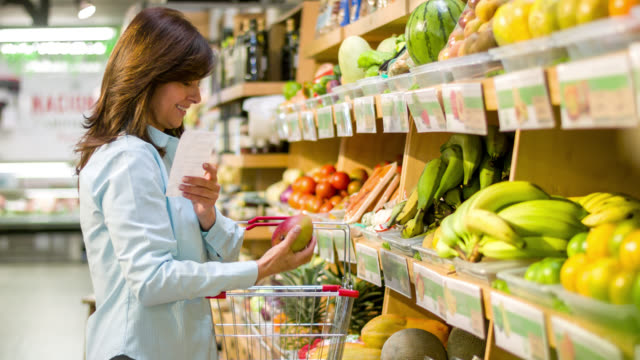 woman at the supermarket with a shopping list - homemaker stock videos and b-roll footage
