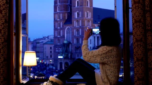 vídeos de stock, filmes e b-roll de mulher na janela tirar foto de cracóvia - peitoril de janela