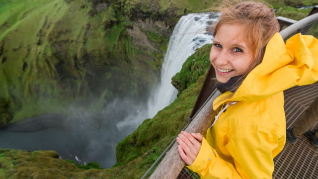 woman at top of iceland's waterfall skogafoss smiling into camera - windswept stock videos & royalty-free footage