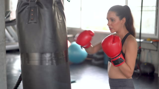 woman athlete training kickboxing exercise workout punching bag tough female fighter practice boxing in gym enjoying fitness lifestyle - kickboxing stock videos & royalty-free footage