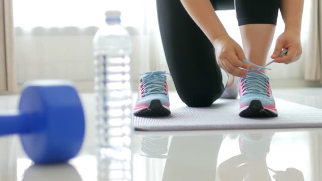 Woman athlete tying blue sports shoe with exercise equipment ay fitness gym