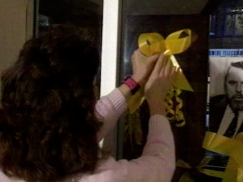 vidéos et rushes de woman attaches yellow ribbons next to a photograph of terry waite to celebrate the news that he has been released from captivity. november 1991. - noeud ruban