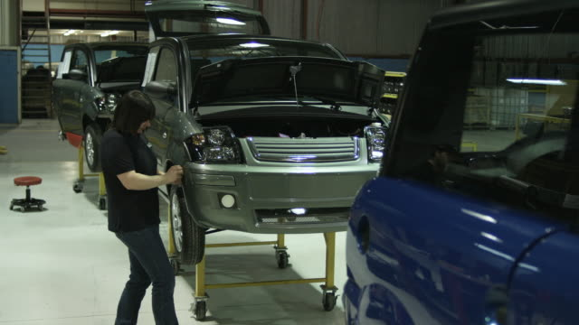 ws woman attaching bumper to electric car on production line, st. jerome, quebec, canada - 自動車工場点の映像素材/bロール