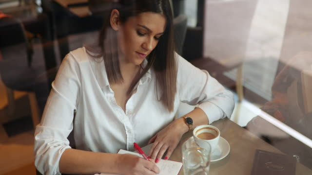 woman author sitting in cafe and writing notes in notebook - author stock videos & royalty-free footage
