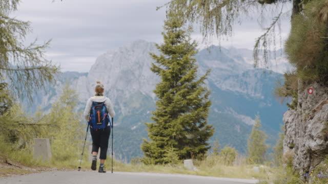 stockvideo's en b-roll-footage met slo mo vrouw backpacker wandelen langs de bergweg - julian alps