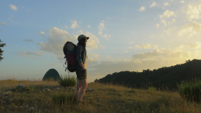 Woman backpacker looking at sunset on the top of a mountain