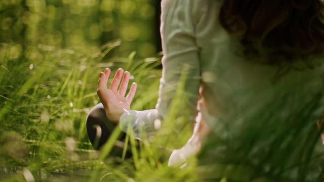 stockvideo's en b-roll-footage met slo mo vrouw balanceert lichaam en geest in het midden van een groene open plek in een zonnig bos - lotuspositie