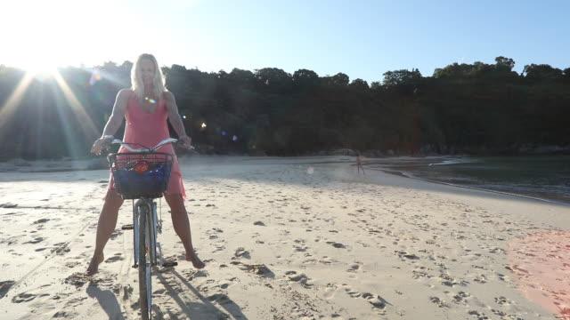 Woman balances on bicycle, on tropical beach