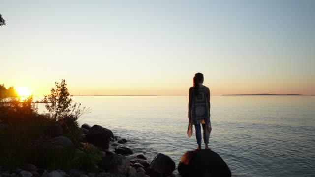 Kvinna saldon på sten i vatten för att titta på färgsprakande solnedgång